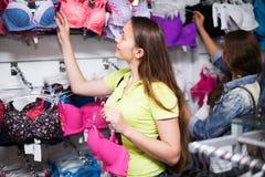 Женщина выбирая нижнее белье в магазине Стоковые Изображения