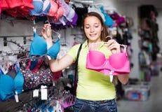 Женщина выбирая нижнее белье в магазине Стоковые Изображения RF
