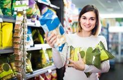 Женщина выбирая очень вкусные закуски в супермаркете Стоковые Изображения