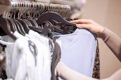 Женщина выбирая одежды в магазине Стоковое фото RF