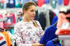 Женщина выбирая свитер во время покупок на магазине одежды Стоковые Изображения RF