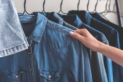 Женщина выбирая статью одежд джинсовой ткани Стоковые Фотографии RF