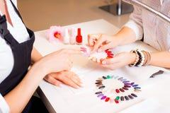 Женщина выбирая цвет маникюра для ее ногтей Стоковые Фотографии RF
