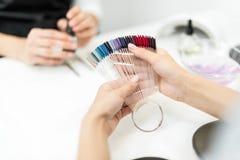 Женщина выбирая цвет маникюра Стоковое Изображение
