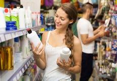 Женщина выбирая шампунь в магазине Стоковые Фотографии RF