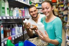 Женщина выбирая шампунь в магазине Стоковое Изображение RF