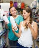 Женщина выбирая шампунь в магазине Стоковое Фото