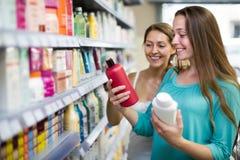 Женщина выбирая шампунь в магазине Стоковое Изображение