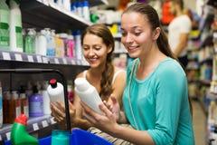 Женщина выбирая шампунь в магазине Стоковая Фотография RF