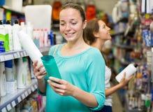 Женщина выбирая шампунь в магазине Стоковые Фото