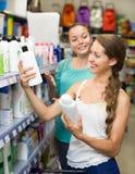 Женщина выбирая шампунь в магазине Стоковое фото RF