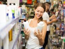 Женщина выбирая шампунь в магазине Стоковая Фотография