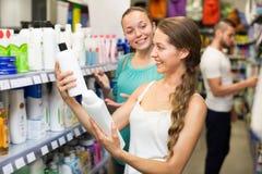Женщина выбирая шампунь в магазине Стоковые Изображения RF