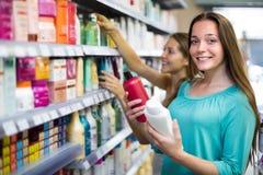 Женщина выбирая шампунь на магазине Стоковое Изображение