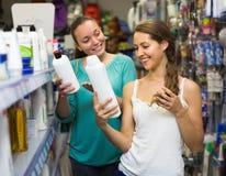 Женщина выбирая шампунь на магазине Стоковые Изображения