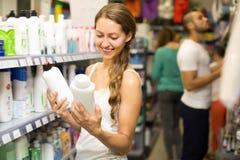 Женщина выбирая шампунь на магазине Стоковые Фотографии RF