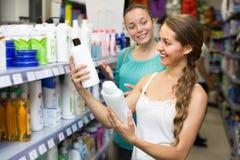 Женщина выбирая шампунь на магазине Стоковое Изображение RF