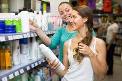 Женщина выбирая шампунь на магазине Стоковая Фотография