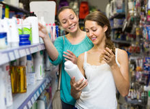 Женщина выбирая шампунь на магазине Стоковая Фотография RF