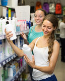 Женщина выбирая шампунь на магазине Стоковое Фото