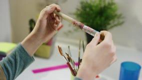 Женщина выбирая щетку для рисовать сток-видео