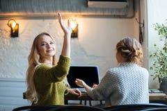 Женщина вызывая кельнера в кафе Стоковая Фотография