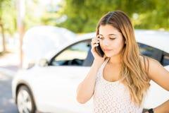 Женщина вызывая кто-то для помощи с ее сломленным автомобилем стоковое фото rf