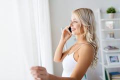 Женщина вызывая на smartphone на окне в утре стоковые изображения rf