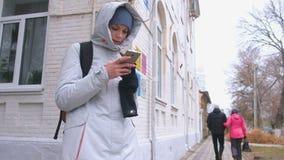Женщина выпаданная из ускорения в городе и искать маршрут используя навигатора в мобильном телефоне видеоматериал