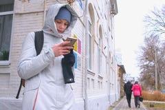 Женщина выпаданная из ускорения в городе и искать маршрут используя навигатора в мобильном телефоне стоковое изображение rf