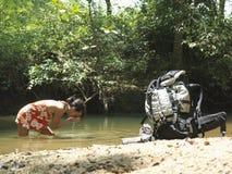 Женщина выпивает воду в озере с рюкзаком на береге Стоковые Фото