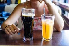 Женщина выпивает коктеиль и пиво в кафе Стоковая Фотография