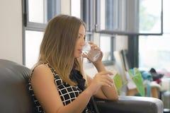 Женщина выпивает пилюльку от боли стоковые изображения rf