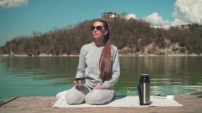 Женщина выпивает чай от thermos в солнце, сидя на деревянной пристани озера на весенний день, ослабляя в природе видеоматериал