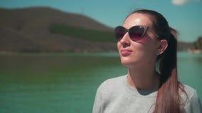 Женщина выпивает чай от thermos в солнце, сидя на деревянной пристани озера на весенний день, ослабляя в природе акции видеоматериалы