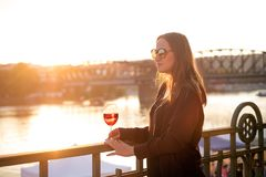 Женщина выпивая вино в городе во время захода солнца стеклянное красное вино Концепция свободного времени в городе и выпивая спир Стоковое Изображение RF