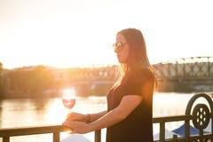Женщина выпивая вино в городе во время захода солнца стеклянное красное вино Концепция свободного времени в городе и выпивая спир Стоковая Фотография RF