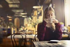 Женщина выпивая в кафе стоковая фотография rf