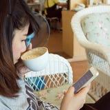 Женщина выпивая горячий кофе в кафе и использует мобильный телефон стоковая фотография rf