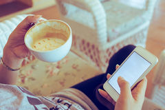 Женщина выпивая горячий кофе в кафе и использует мобильный телефон стоковые изображения