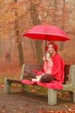 Женщина выпивая горячий кофе ослабляя в парке осени Стоковая Фотография