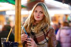 Женщина выпивая горячий пунш на немецкой рождественской ярмарке Стоковое фото RF