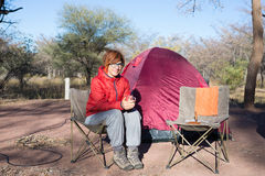 Женщина выпивая горячую кружку кофе пока ослабляющ в месте для лагеря Шатер, стулья и оснащения для кемпинга Мероприятия на свеже Стоковые Изображения RF