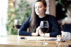 Женщина выпивая красное вино в кафе и имея остатки около окна стоковое фото rf