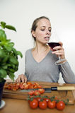 Женщина выпивая красное вино пока варящ Стоковое фото RF