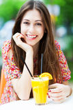 Женщина выпивая оранжевый коктеиль Стоковое фото RF