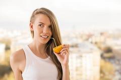 Женщина выпивая от апельсина Стоковые Фотографии RF