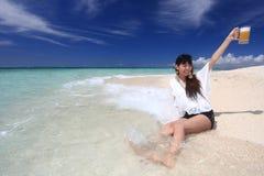 Женщина выпивая пиво на пляже стоковая фотография