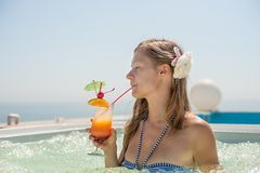 Женщина выпивая тропический коктеил Стоковая Фотография