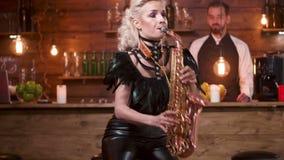 Женщина выполняет на саксофоне перед счетчиком бара акции видеоматериалы